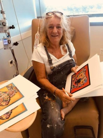 On her first day of chemotherapy at Mariners Hospital, Maxine Trainer brings out some of her favorite prints. The artist eventually would redecorate the bare walls of all the infusion rooms. CONTRIBUTED