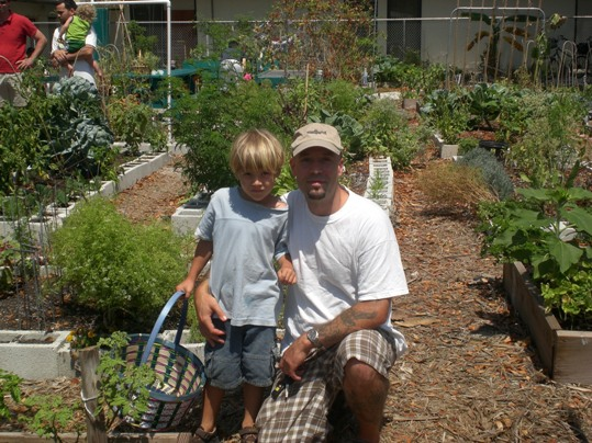 Community Garden Board Member Will Shepler and his son Liam collect their harvest from their plot