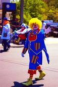 Clown waving at parade goers as he marches down Saco Ave.