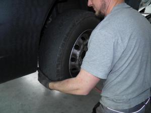 Wir packen an. Hier sehen Sie einen Facharbeiter der einen Reifen wechselt