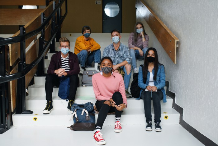 Front,View,Of,Young,Students,With,Face,Masks,Back,At