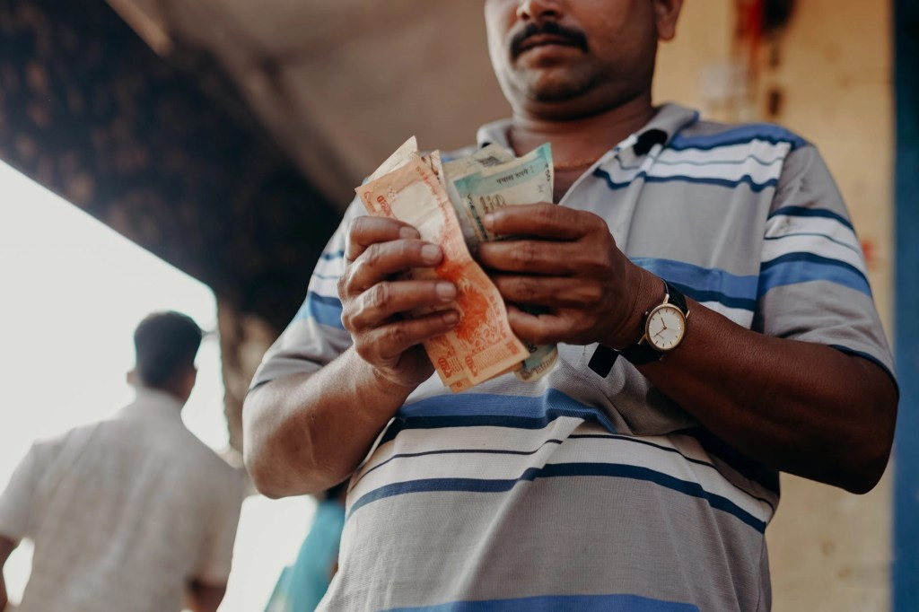 man in blue and white stripe polo shirt holding banknote