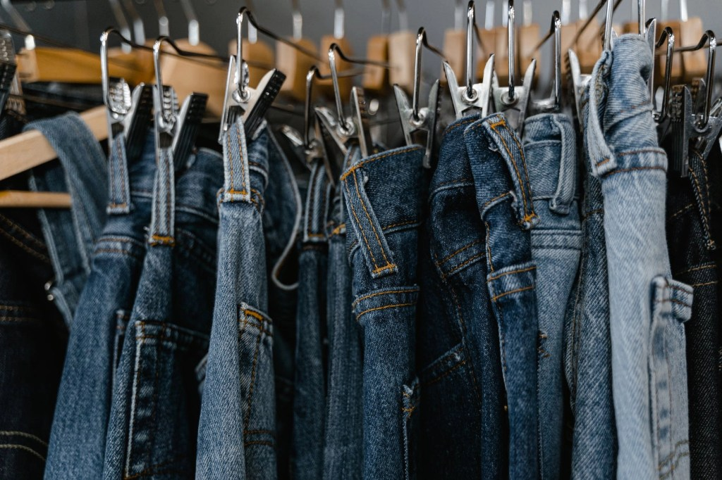 close up photo of denim jeans on a clothing rack