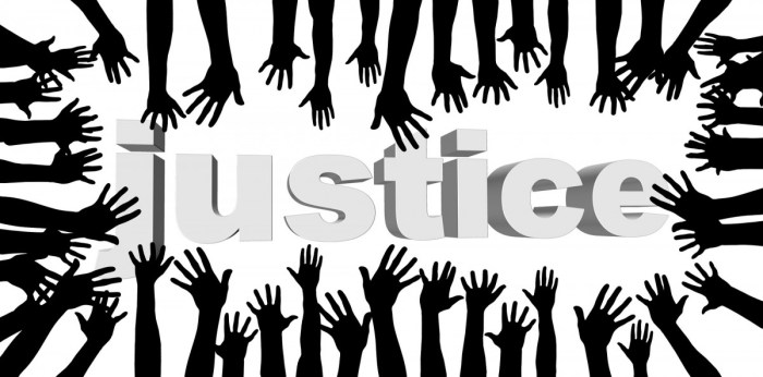 Image of many hands reaching towards the word 'justice'.