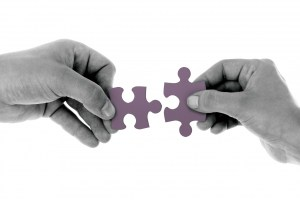 Image of hands holding jigsaw puzzle pieces