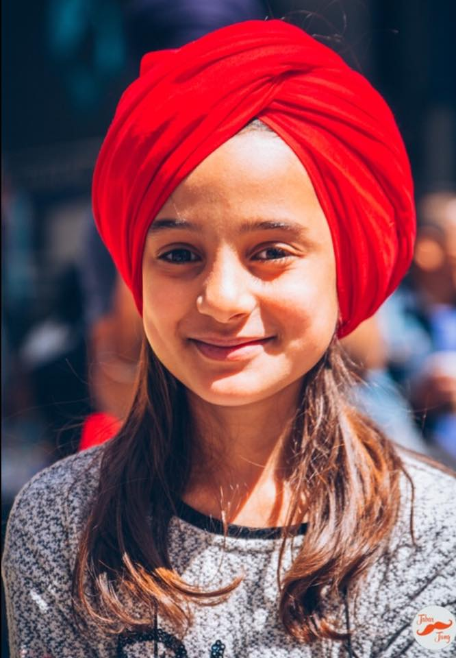 A young girl gets a turban
