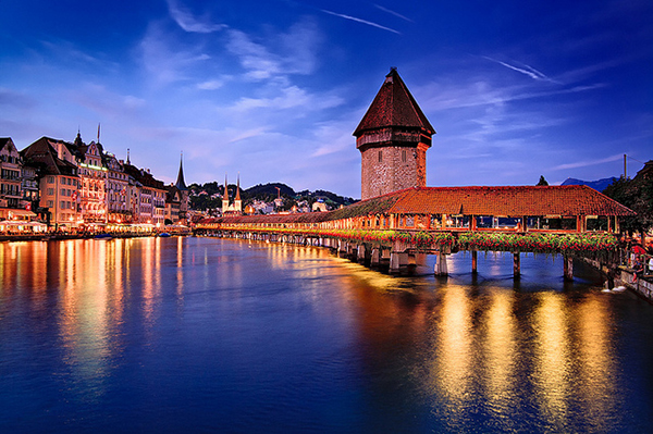 The city of Lucerne straddles the Reuss River, therefore it has many bridges. The most famous is the Chapel Bridge, a 204 m long wooden bridge originally built in 1333. Part way across, the bridge runs by the octagonal Water Tower (Wasserturm), a fortification from the 13th century. Inside the bridge are a series of paintings from the 17th century depicting events from Luzern's history. The Bridge with its Tower is the city's most famous landmark.