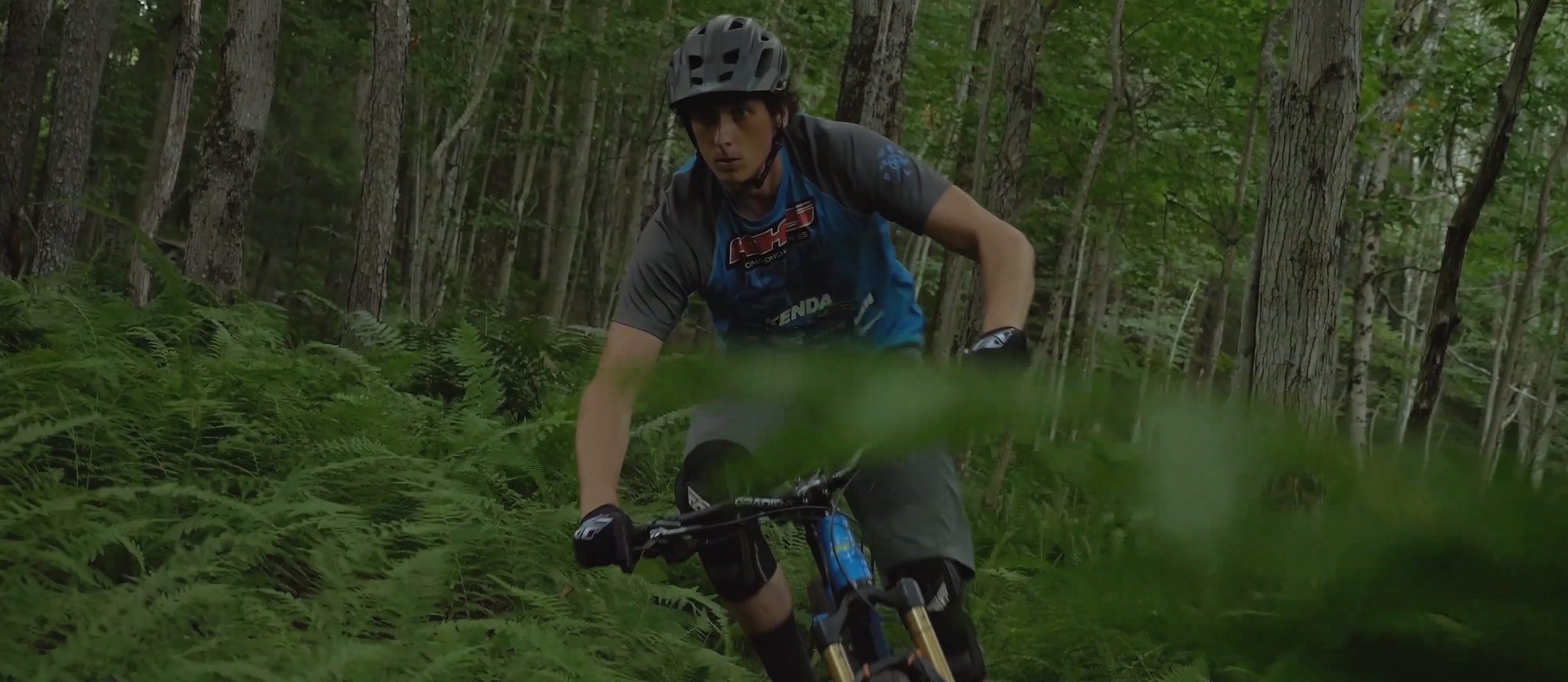 KHS pro mtb rider, Seamus Powell, riding through the woods.