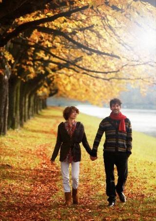 Couple strolling through park in autumn -Khurki.net