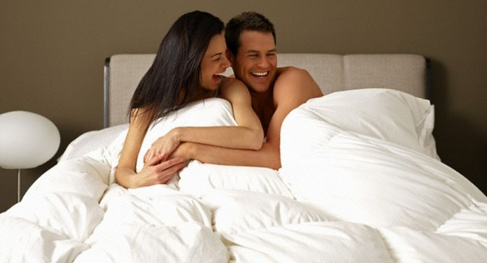 Laughing Couple in Bed --- Image by © Larry Williams/Corbis