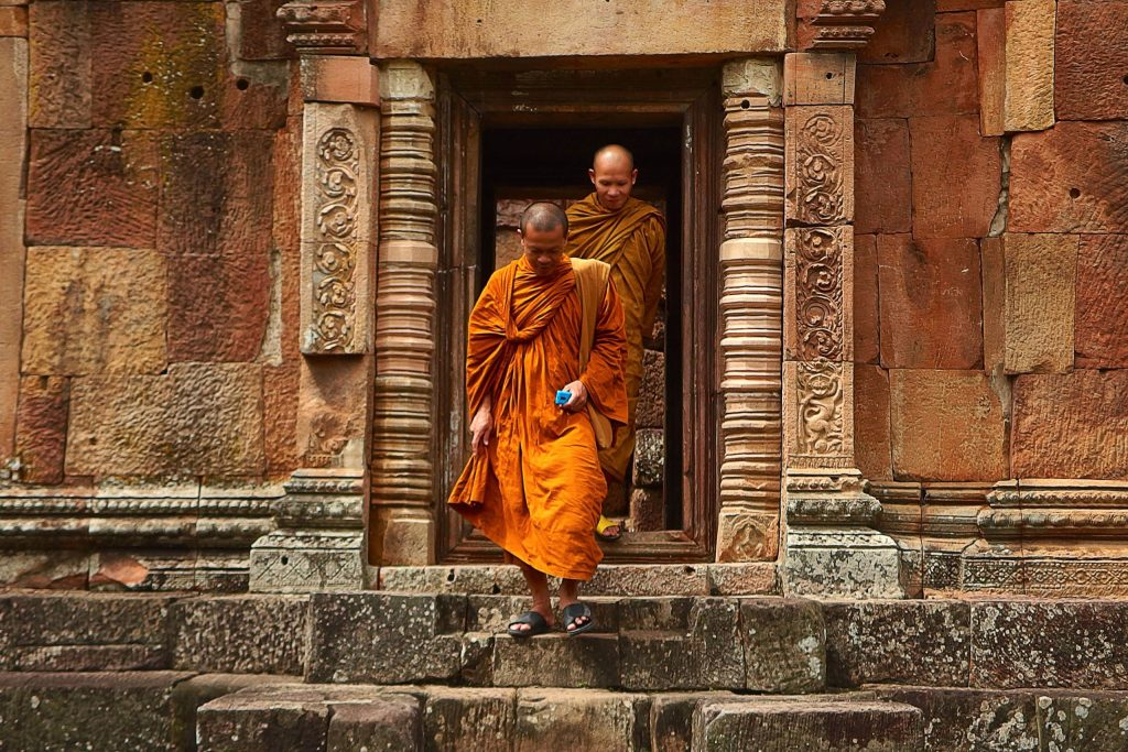 Two monks stepping out of the wat (or a temple) in Chiang Mai Thailand.