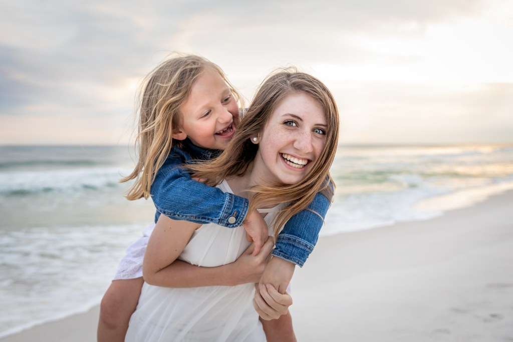 Older sister giving younger sister a piggy back ride on Okaloosa Island beaches