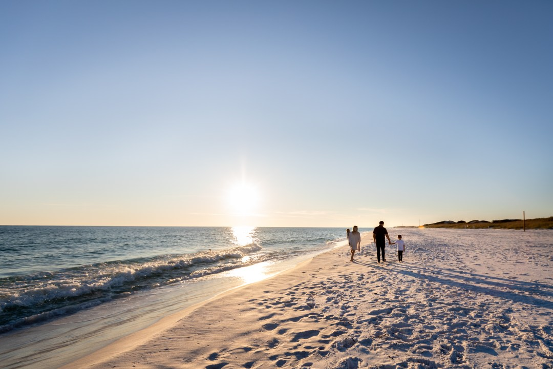 Okaloosa Island family photo session walking toward sunset