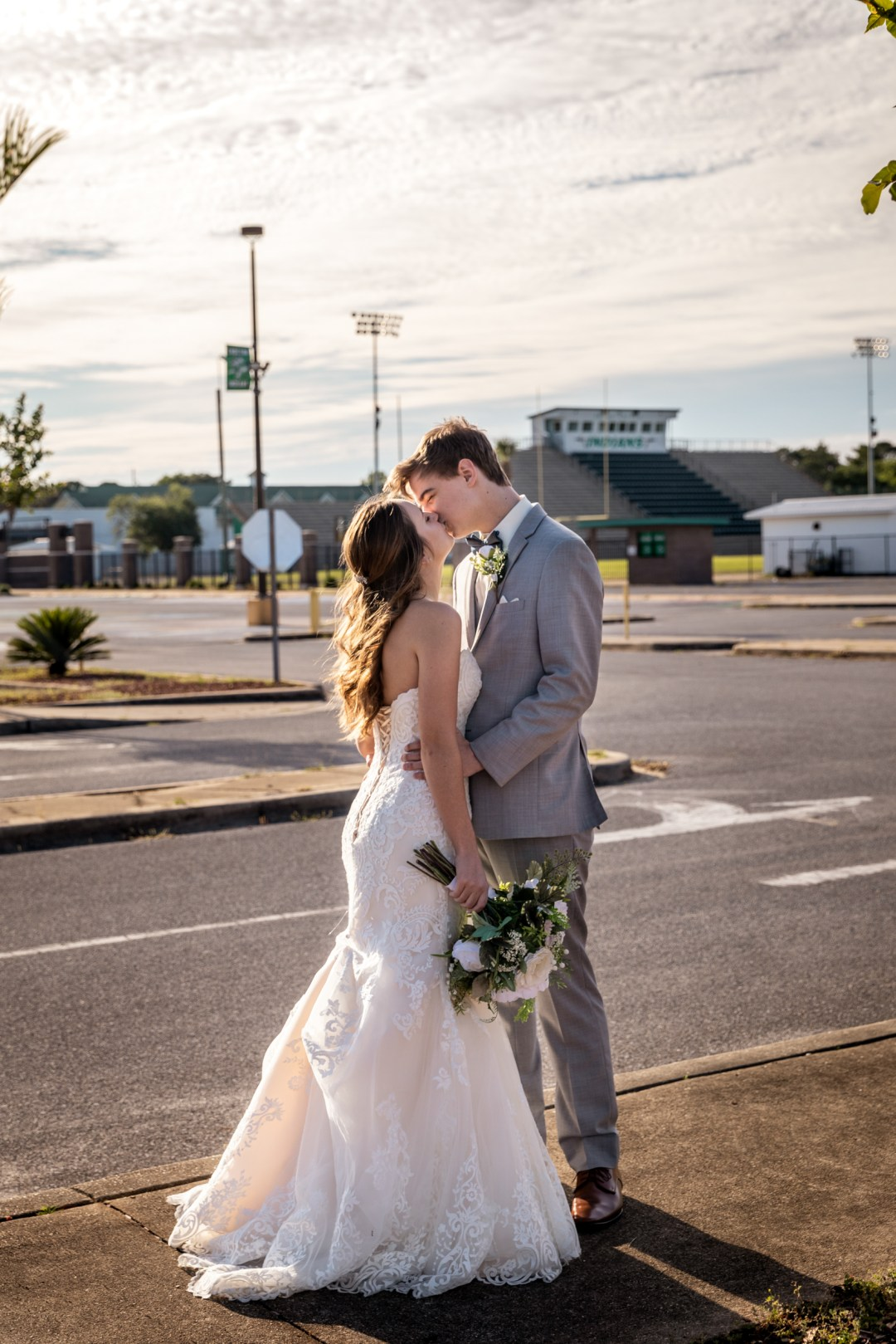 bride and groom kiss in front of high school football field