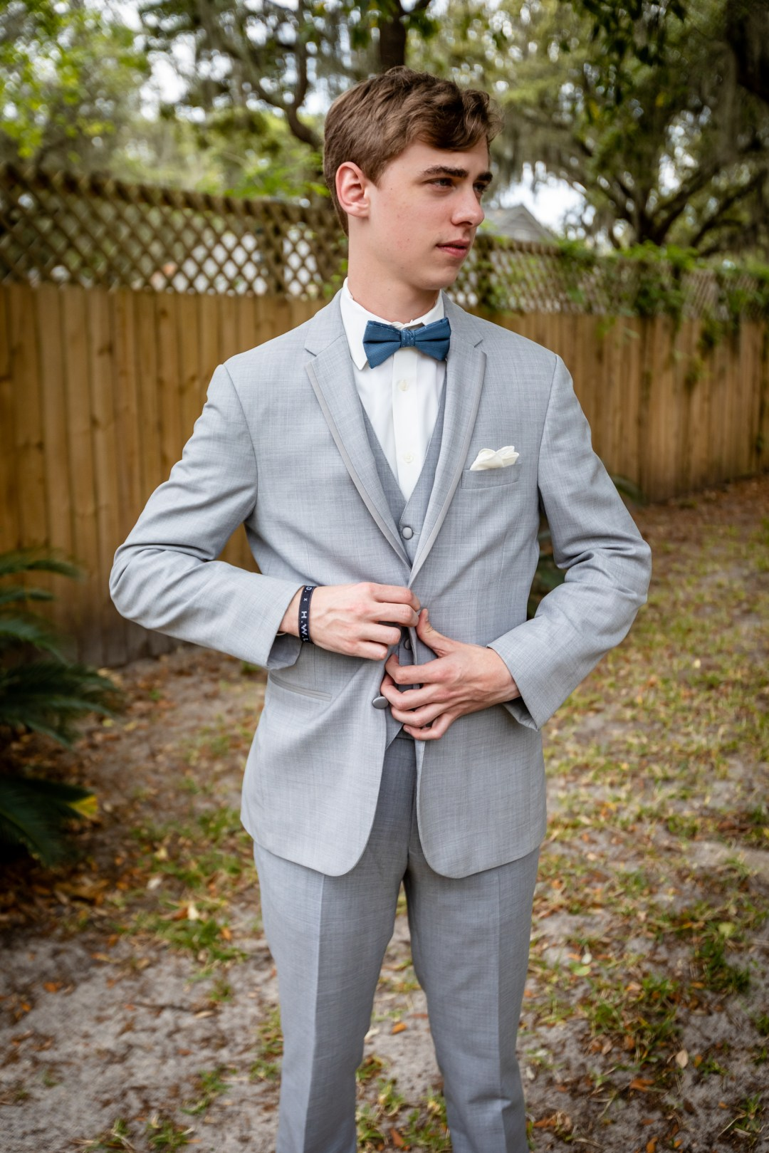 groom buttoning tuxedo before wedding ceremony