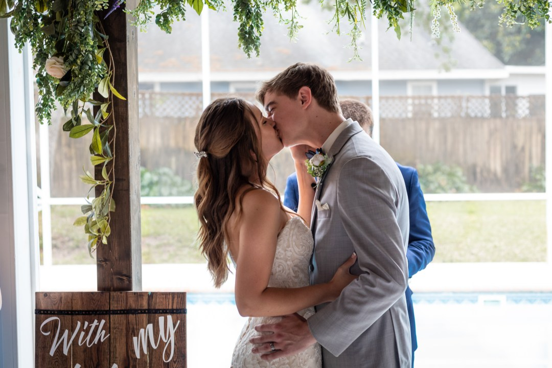 bride and groom kiss during COVID-19 wedding video