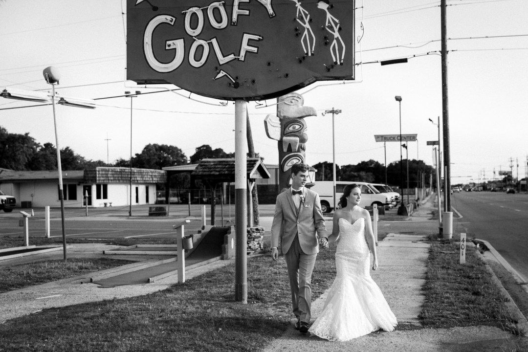 Bride and groom walking by closed Goofy Golf due to COVID-19