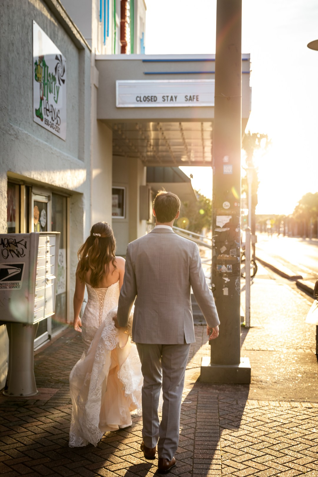 COVID-19 wedding video shot of bride and groom walking by closed theater in downtown Fort Walton Beach