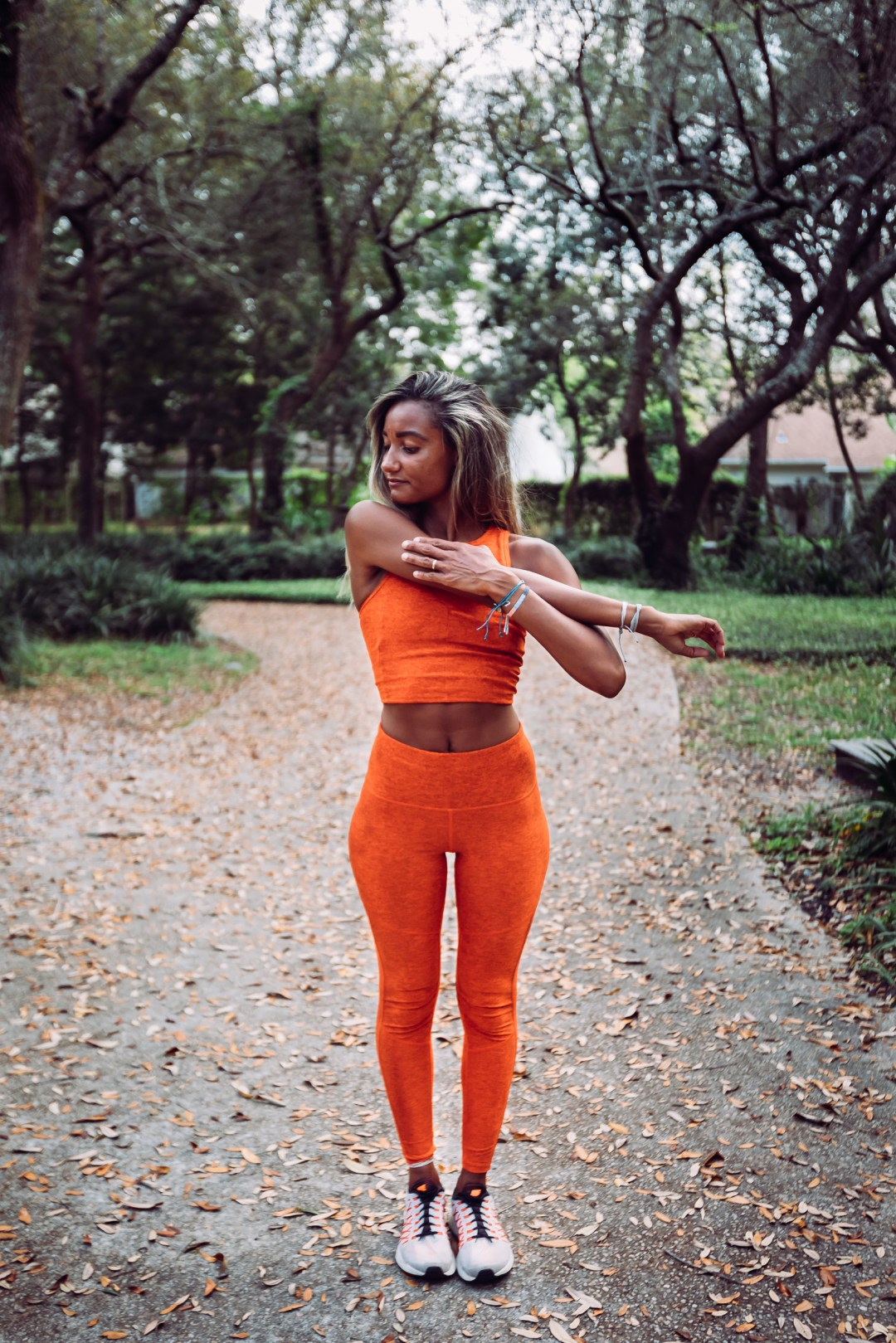 fitness coach stretching in park and posing for brand photos