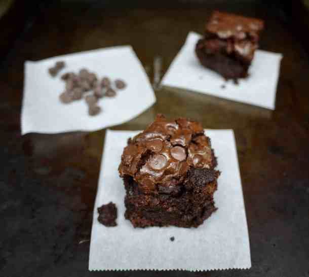 Kickass brownies on parchment squares on sheet tray with chocolate chips