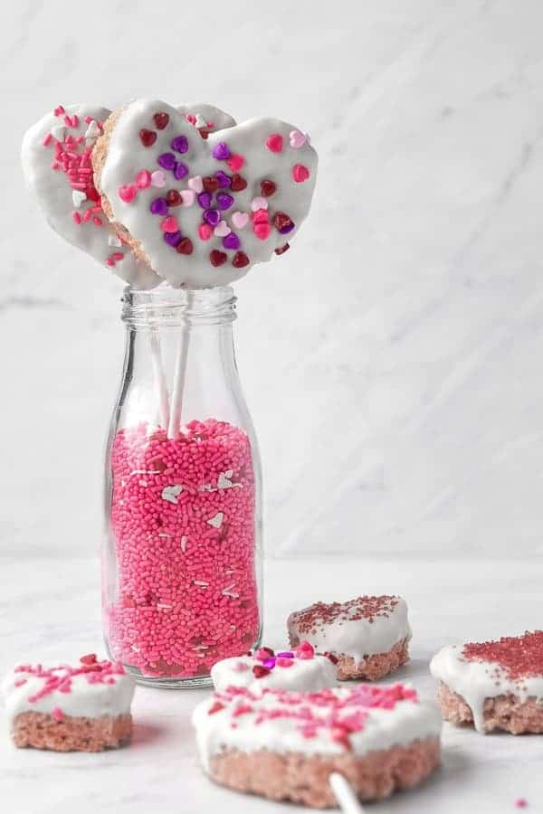 White Chocolate-dipped Rice Krispie Treats | kickassbaker.com #valentinesday #treats #vday #love #ricekrispietreats #ricekrispies #whitechocolate #almondbark #sprinkles #kidstreat #funwithkids #easyrecipes #forkids #nutfree