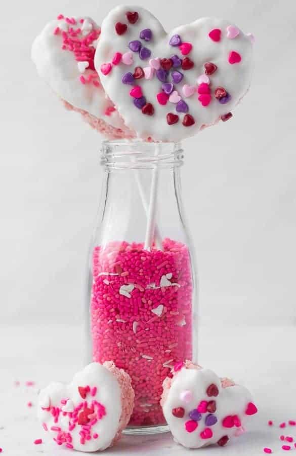 White Chocolate-dipped Rice Krispie Treats | kickassbaker.com #valentinesday #treats #vday #love #ricekrispietreats #ricekrispies #whitechocolate #almondbark #sprinkles #kidstreat #funwithkids #easyrecipes #forkids #nutfree