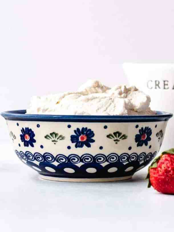 Vanilla Whipped Cream in an ornate blue bowl with strawberry on the side