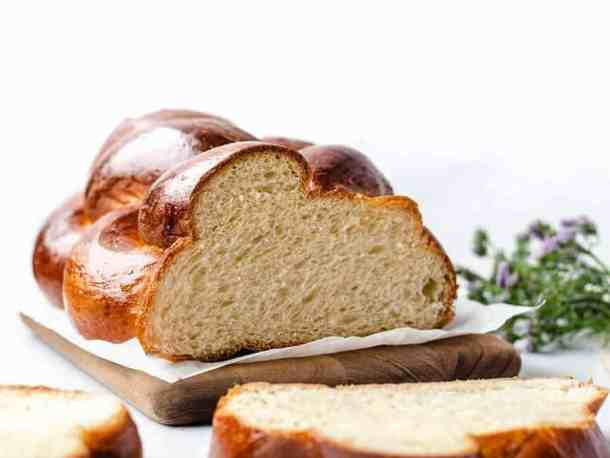 Challah Bread horizontal sliced on cutting board with flowers behind | kickassbaker.com