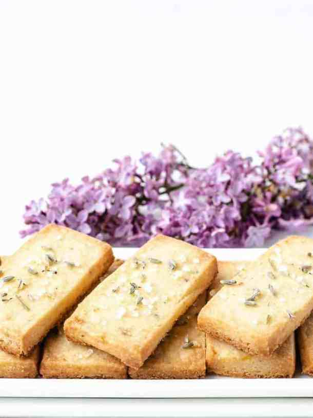 Lavender Lemon Shortbread Cookies stacked neatly on a white plate with purple flowers behind vertical orientation