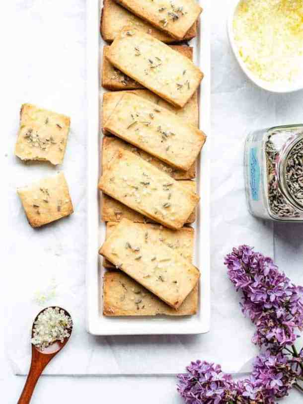 Overhead shot of lavender lemon shortbread cookies stacked neatly on a white rectangular plate with purple flowers and lemon sugar to the right