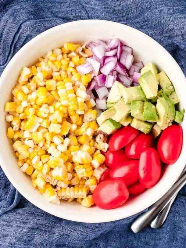 Overhead shot of ingredients for corn salad in a bowl ready to be mixed together, spoons off to the side on a blue cloth background