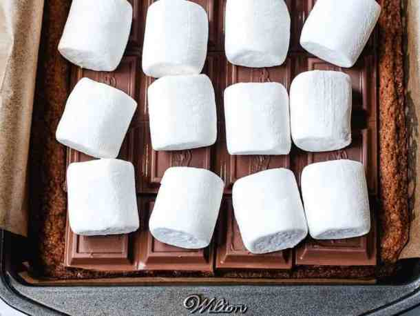 Overhead shot of marshmallows laying on top of graham cracker crust and Ghiradelli caramel bars