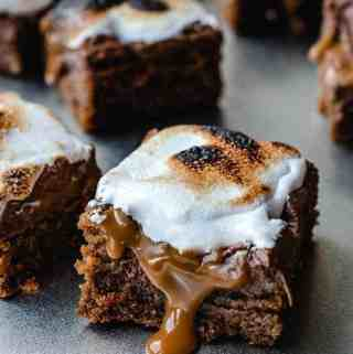 Caramal S'mores bar with toasted marshmallow and caramel dripping down the side of the bar