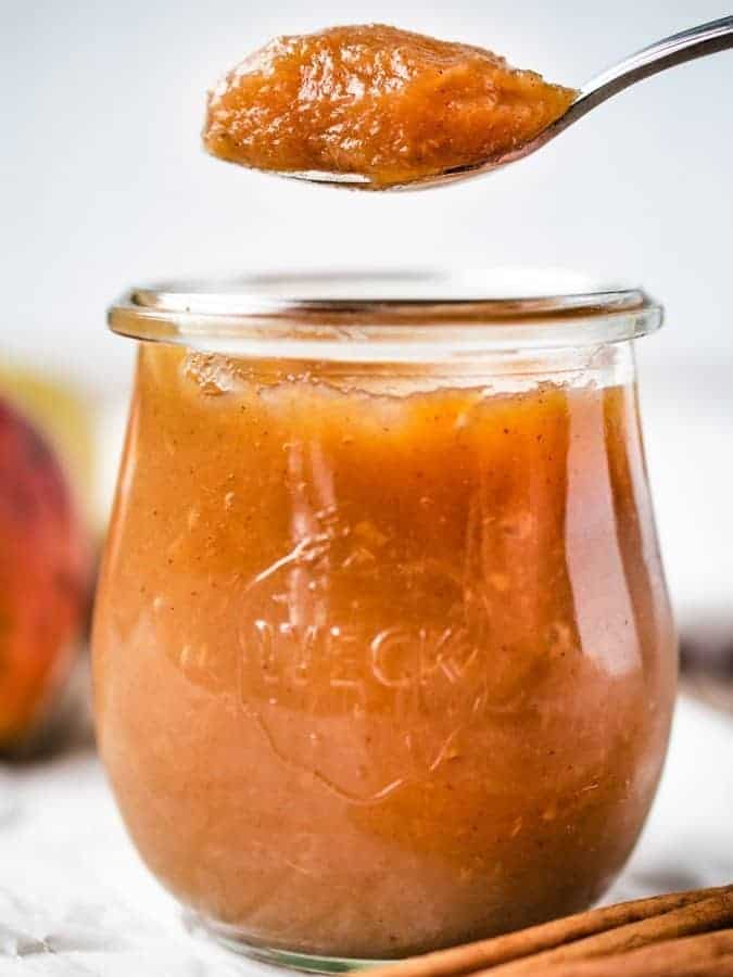 Jar of homemade applesauce with spoonful being taken out