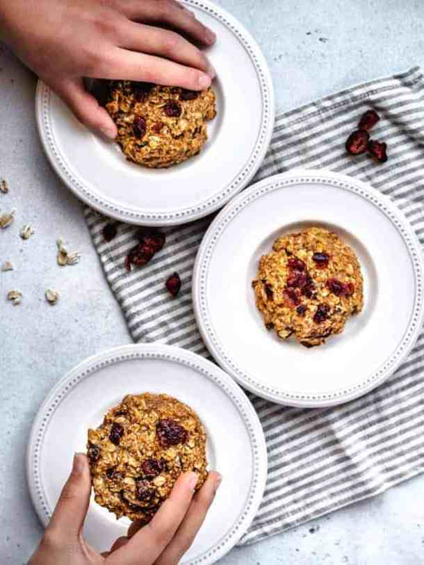 two hands grabbing for gluten- free breakfast cookies on white plates