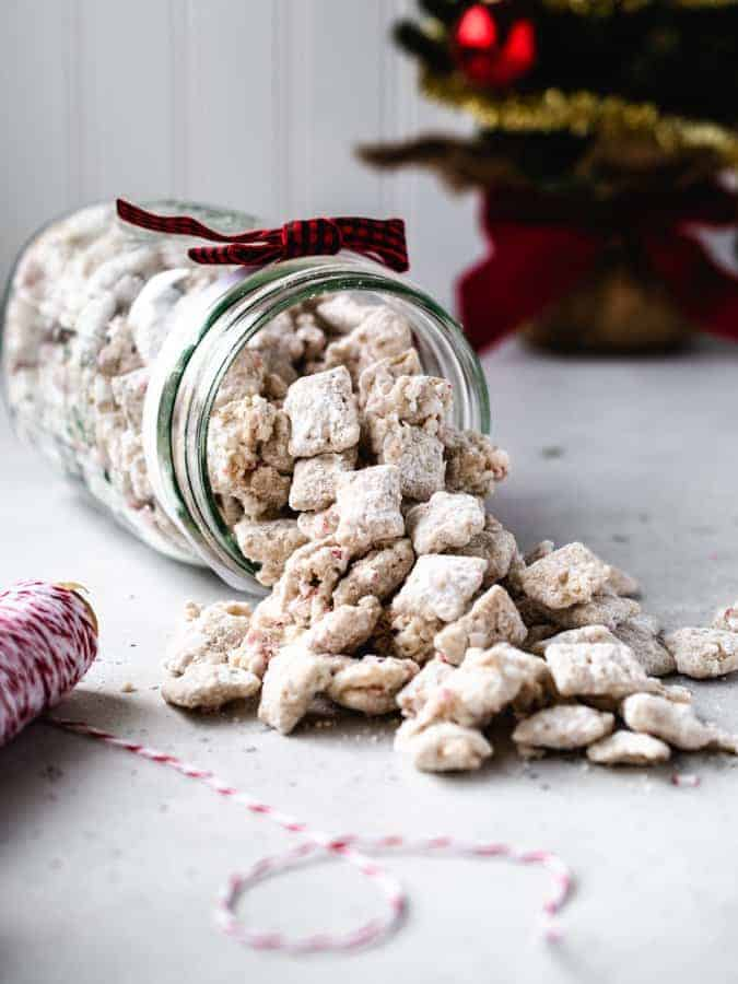 Jar of peppermint puppy chow spilling out on table with christmas tree behind