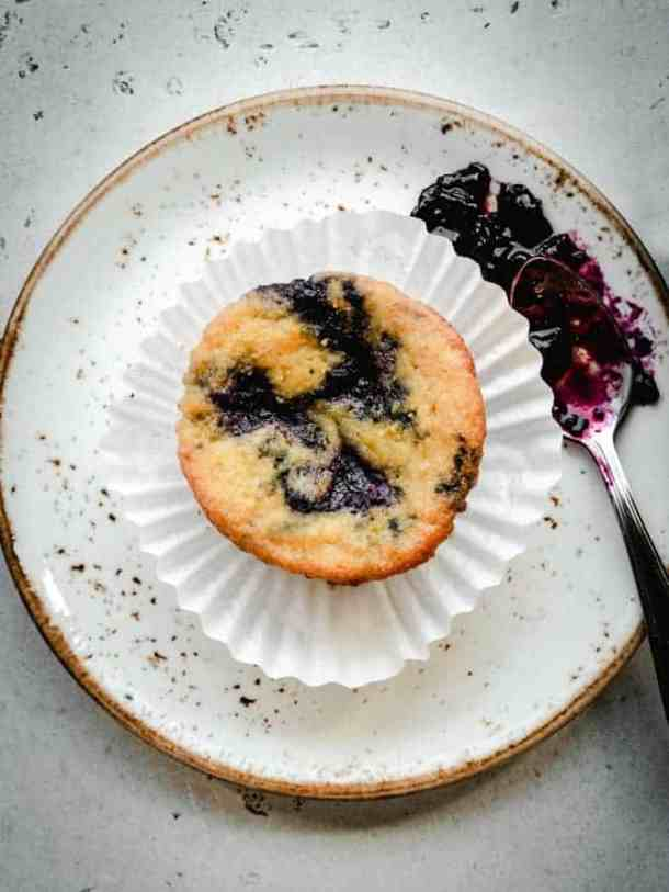 overhead of a single lemon muffin swirled with blueberry jam on a plate