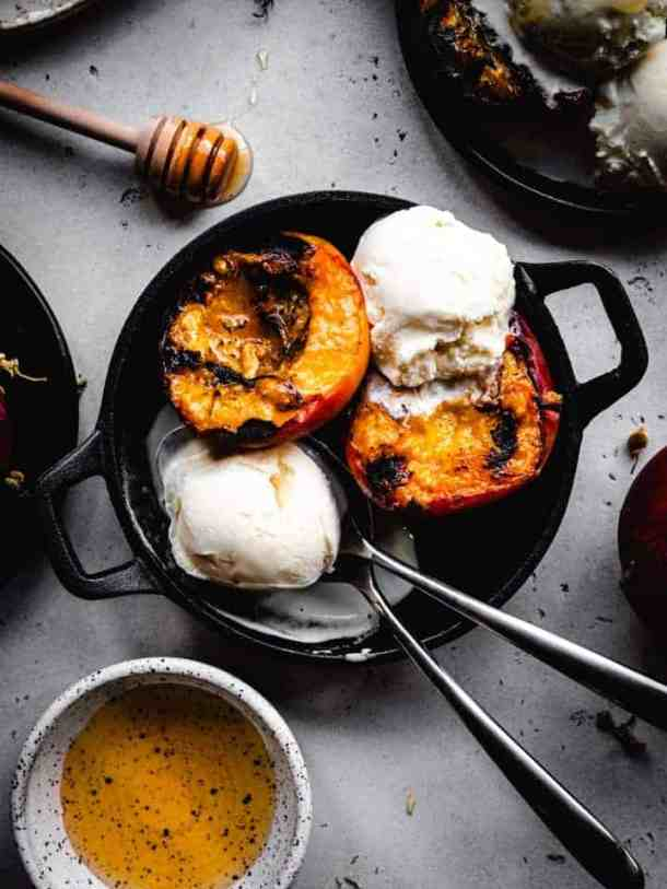 grilled peaches with ice cream scoops in a small cast iron dish