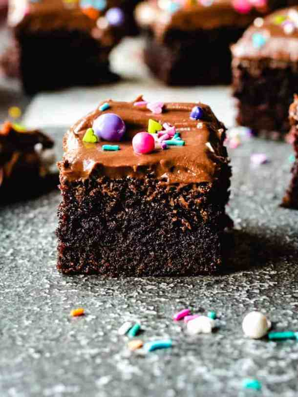 slices of easy one bowl chocolate cake with chocolate frosting and sprinkles