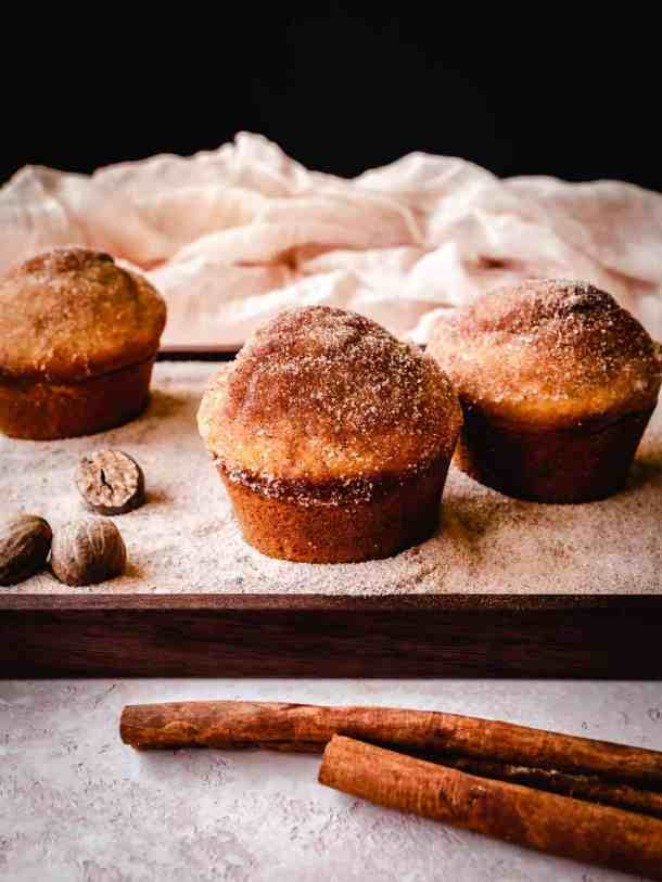 cinnamon sugar donut muffins on a wood plate with whole nutmeg and cinnamon sticks
