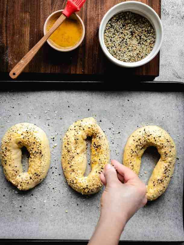 sprinkling everything bagel seasoning on homemade Jerusalem Bagels