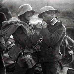 Een Duitse krijgsgevangen soldaat geeft een gewonde Engelse soldaat, een Tommy, een vuurtje voor het aansteken van een sigaret tijdens de Eerste Wereldoorlog, plaats en jaartal onbekend.