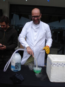A scientist dips a hose funnelling dry ice fumes into washing up liquid