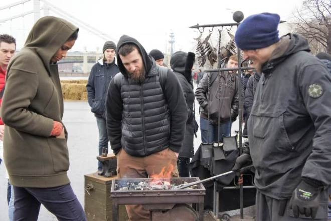 Two men and a woman stand around a small forge next to the Moscow River in Gorky Park. The woman is looking down, with her hood up and her hands in the pocket of her coat and operating bellows with her foot. A man opposite her is smiling and holding a long metal rod in the fire. He has on a beanie hat and a cagoule and some gloves. The other man stands between them with his hands in the pockets of his trousers, looking at the fire. He is wearing a hoody and a bodywarmer.