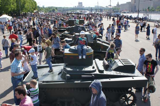 There are a whole bunch of people climbing over tanks parked on the embankment of the Moscow river in Gorky Park
