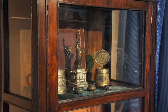 A display cabinet at the Tchaikovsky House Museum which has a Statue of Liberty souvenir in it.