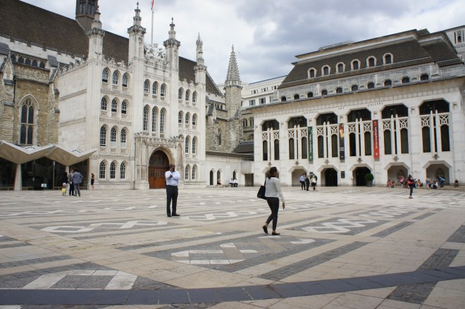 Guildhall Yard, with the medieval Guildhall to the left and the 20th century art galley building to the right. In th foreground you can see a curved line which represents the perimeter of the amphitheatre. People are walking or standing in the square.