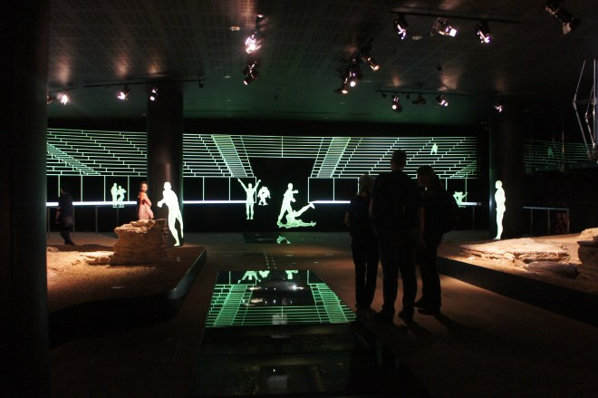 Some people stand in a darkened room containing some ruins from a Roman amphitheatre. Glowing green digitally projected figures and seats give an impression of what it may have looked like.
