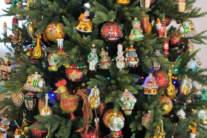 A number of New Year and Christmas tree ornaments hang on a tree