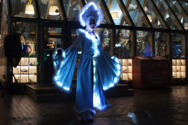 A woman dressed as Snegurochka the snow maiden stands in the dark, all lit up